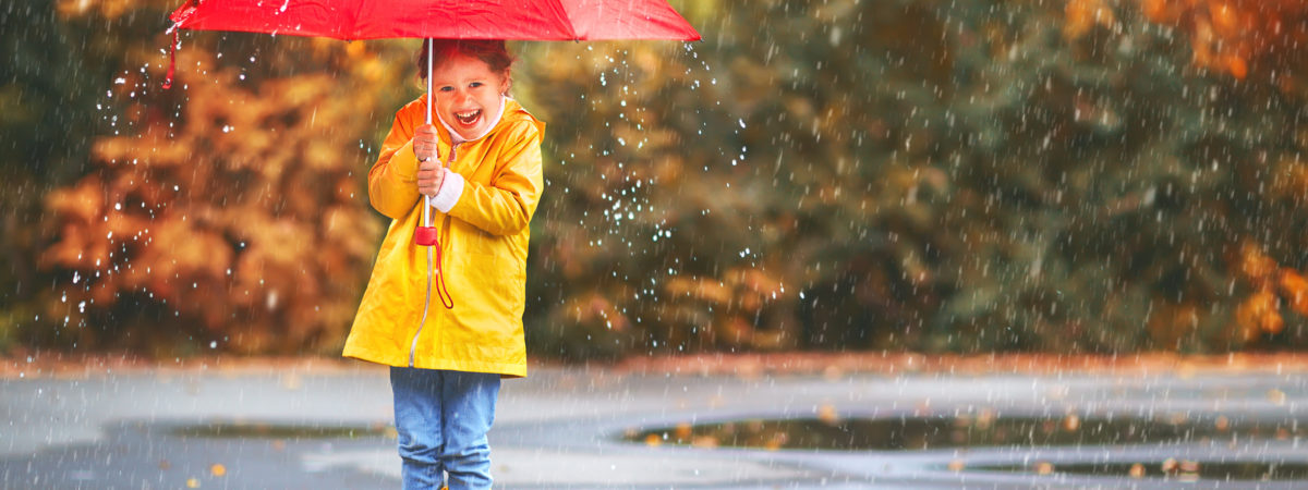 happy child girl with an umbrella and rubber boots in puddle on an autumn walk